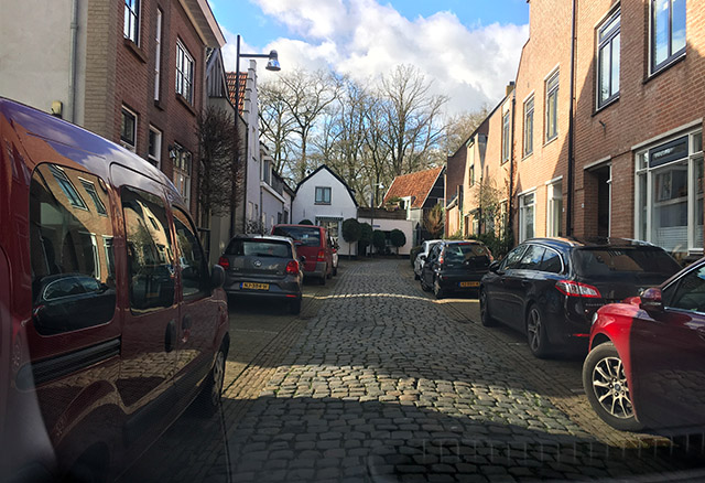 Je rijdt op een éénrichtingsweg. aan de linkerkant en rechterkant van de weg staan veel auto's geparkeerd. waarmee hou je rekening?